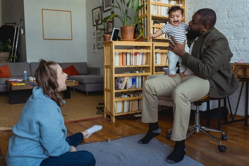 Diverse family members spending time together at home with little kid and sitting on floor and holding baby on knees