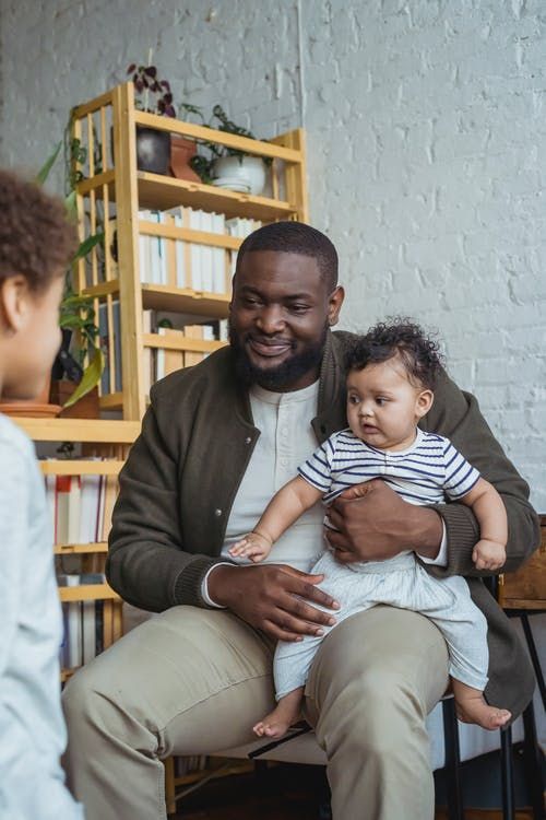 Happy African American dad sitting on chair at home and holding little baby and looking at elder son