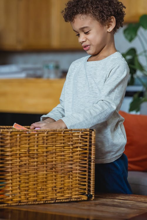 Little kid with curly hair in casual outfit playing at home with toys from wicker basket