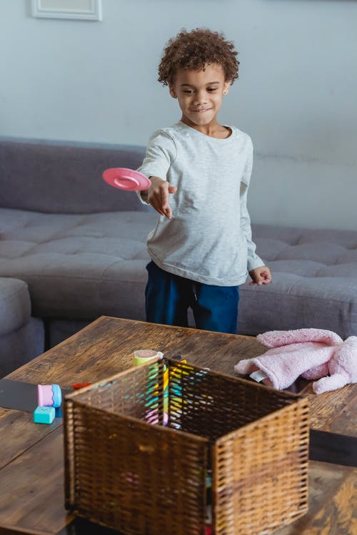Smiling little child in casual apparel dropping pink plastic plate in wicker basket placed on wooden table in living room