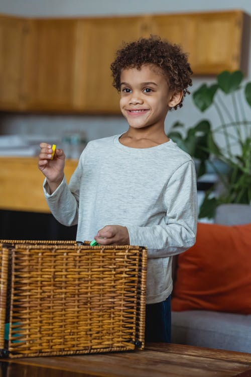 Ethnic boy in casual clothes standing near wooden table in front of wicker box with toys and holding yellow detail of constructor and smiling