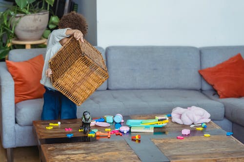 Little boy turning over wicker basket with plastic toys