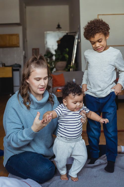 Happy mom sitting on floor and teaching baby to stand on feet and elder kid looking at sibling