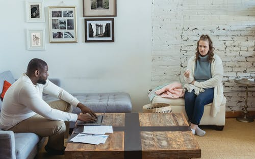 Full body of multiracial couple sitting in living room and sorting things out
