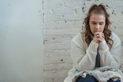 Young pensive female sitting near white wall and pondering unpleasant situation of argument with husband