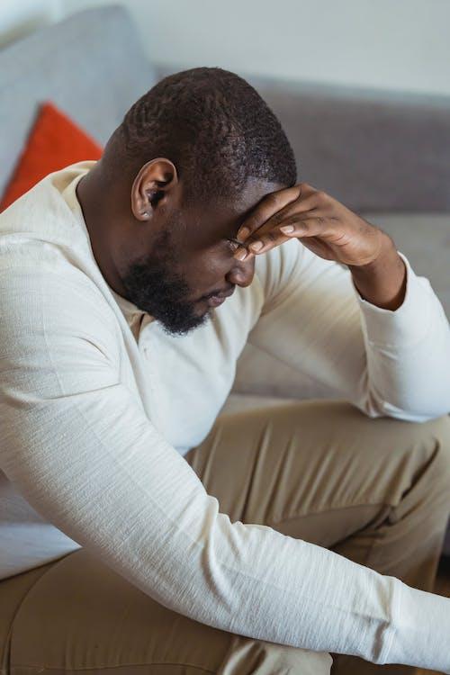 Pensive black man sitting on sofa with bowed head