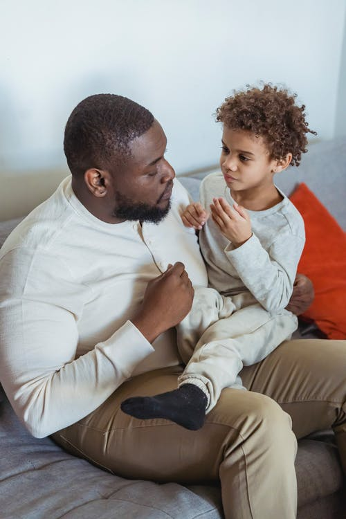From above of African American father holding little child and having serious conversation while sitting on couch at home