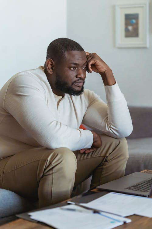 Frustrate black man sitting near laptop and thinking