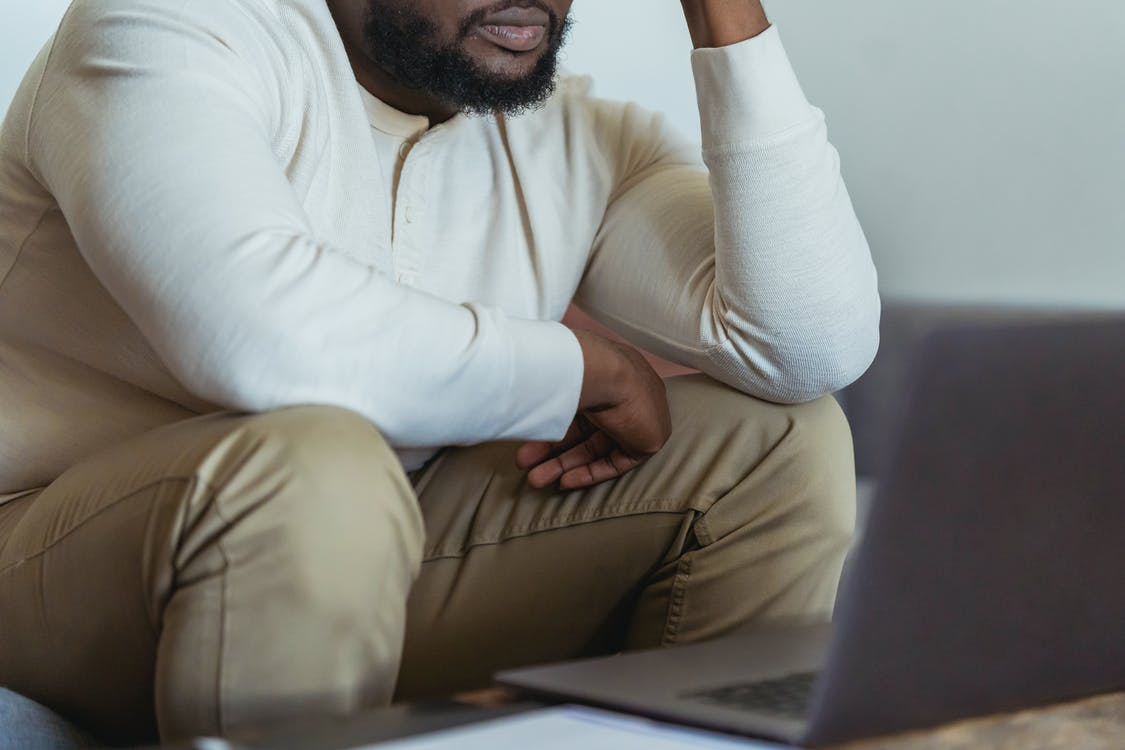 Crop anonymous black male freelancer in casual clothes looking away while sitting and working near laptop
