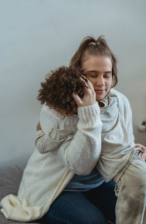 Tender woman with closed eyes embracing loving kid while sitting on sofa and calming down