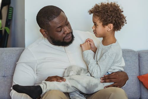 Content African American boy sitting on knees of caring black bearded father on couch in light living room at home