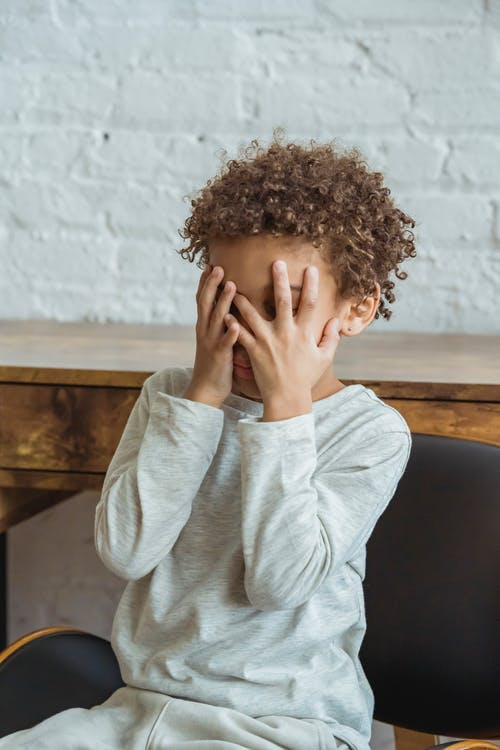 Faceless unhappy black boy in room