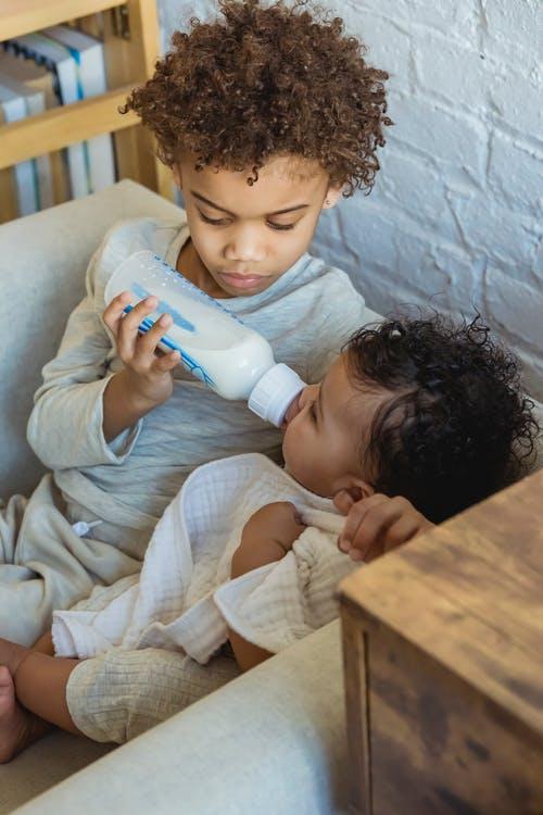 From above of caring African American baby bottle feeding adorable black toddler while sitting in armchair near wall at home