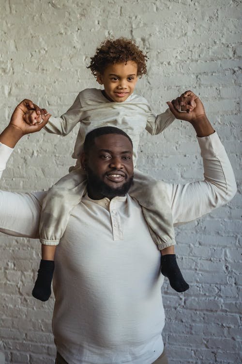 Positive African American man looking away while holding hands of glad black son sitting on shoulders near white wall in room