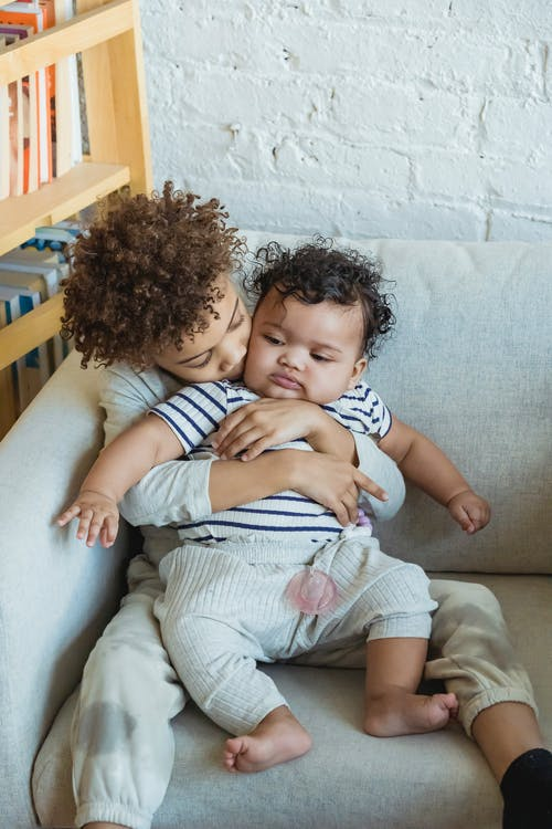 Tender African American boy cuddling adorable little baby while sitting on comfortable sofa near wall in light room at home