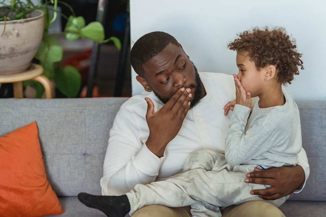 African American man with child in casual outfit covering mouth with hand on couch with pillows while looking at each other in light apartment