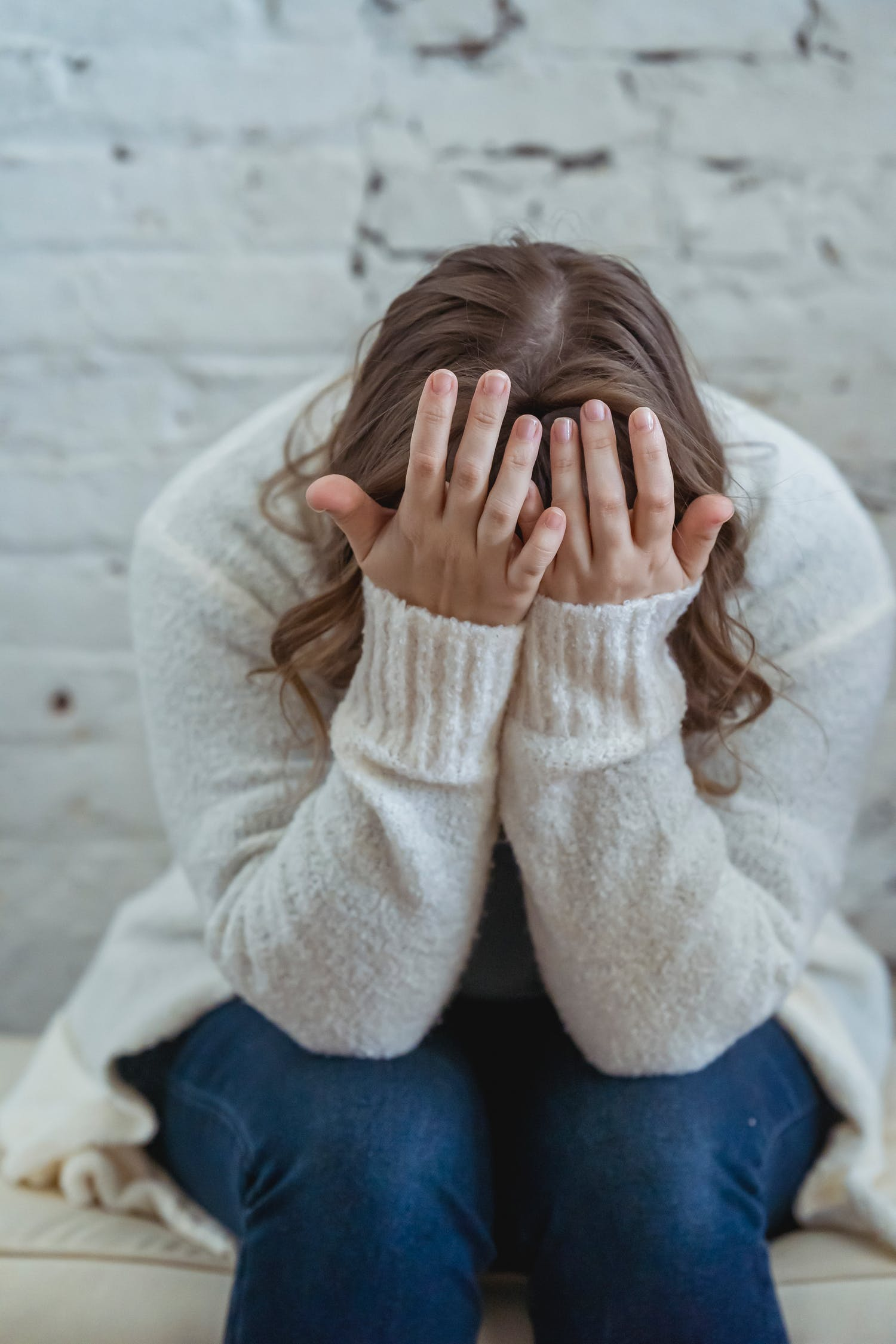 Unrecognizable tired female in casual clothes covering face with hands while sitting on soft surface near brick wall in light apartment