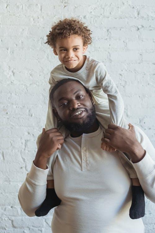 Black male carrying kid on shoulders
