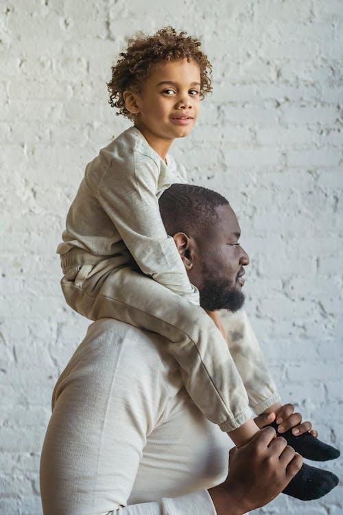 Man in Brown Dress Shirt Carrying Baby