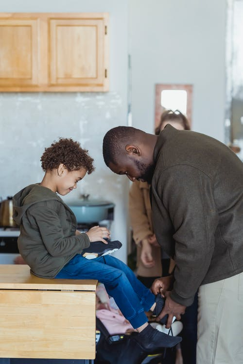 Black father helping son to wear boots near mother