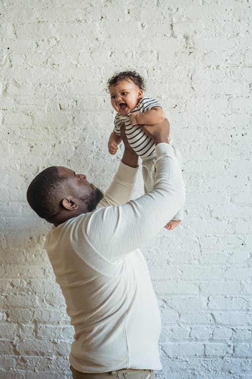 Man in White Long Sleeve Shirt Carrying Baby