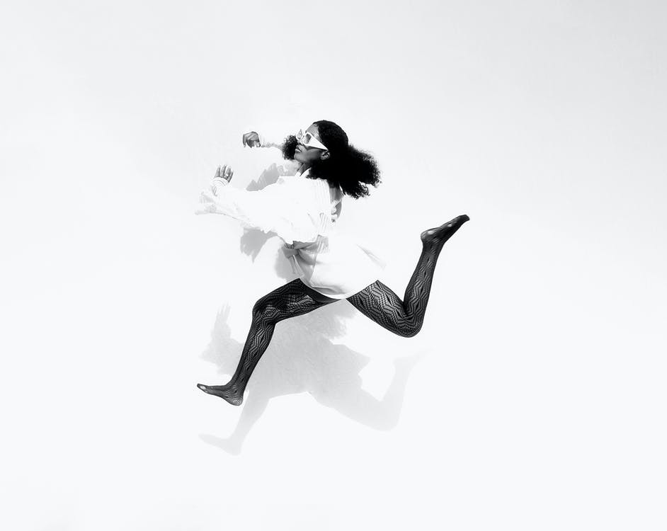 Black and white full body side view of active African American female in sunglasses wearing trendy clothes jumping on white background