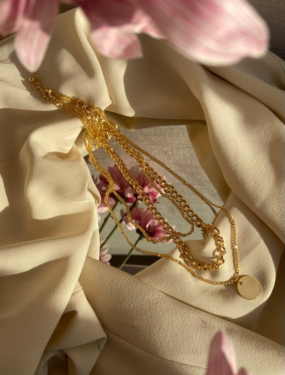 From above of golden chain with pendant placed on crumpled fabric with mirror near pink flowers in light stylish room