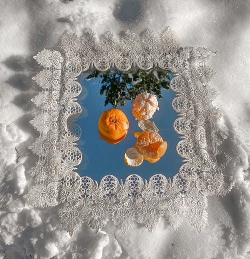 Mirror with tangerines on snowy ground in forest