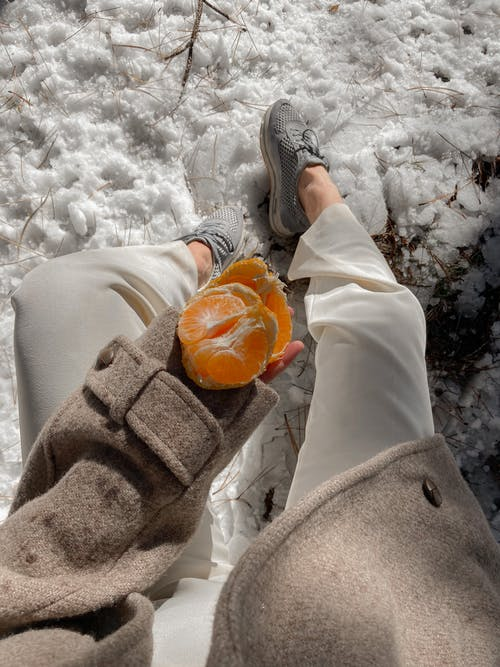 From above of anonymous female in warm coat and ripe peeled tangerine in hand sitting in winter nature with snowy ground