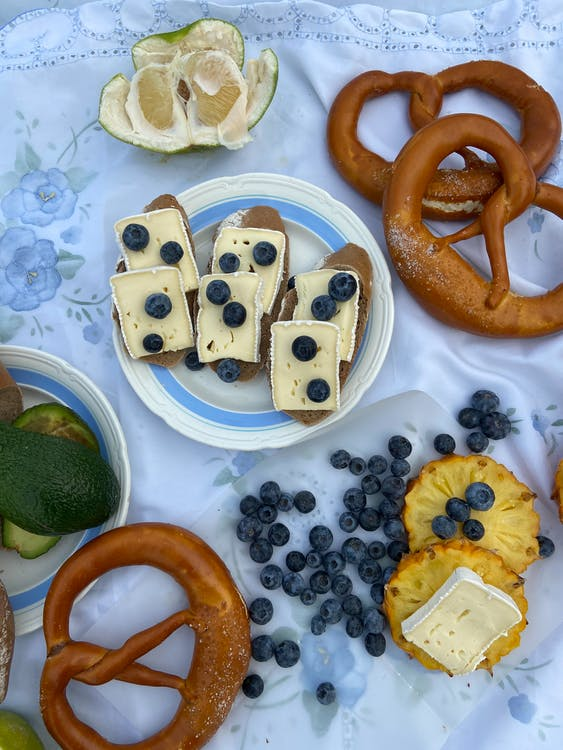 Top view of fresh baked food and loaf with cheese near pineapple with pomelo and scattered blueberries on white plaid