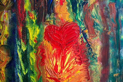 Abstract strokes of multicolored paints randomly smeared on bright surface with red heart shaped drawing in modern studio with art works