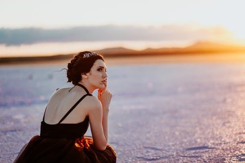 Side view of dreamy young female traveler in elegant black dress sitting on haunches on et sandy beach and looking away thoughtfully against sunset sky