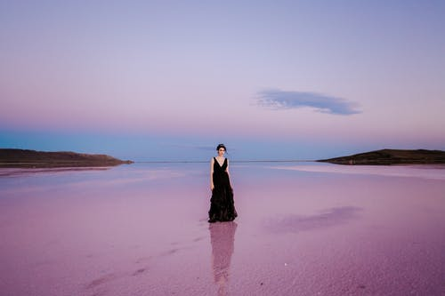 Woman in Black Dress Standing on Brown Sand