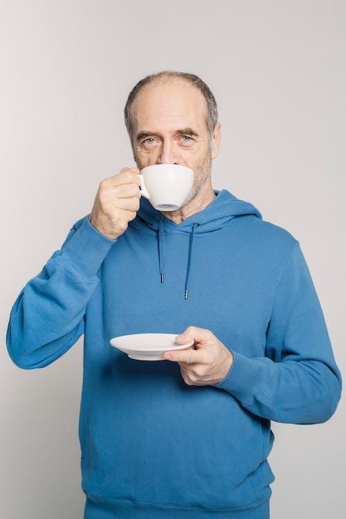 Man in Blue Hoodie Holding White Ceramic Mug