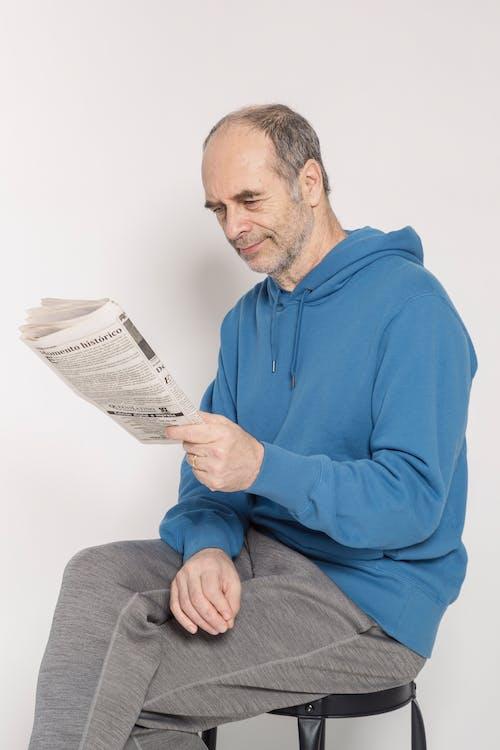 Man in Blue Hoodie Reading Newspaper