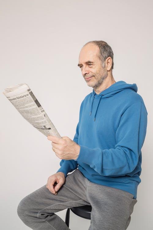 Man in Blue Hoodie Holding Newspaper