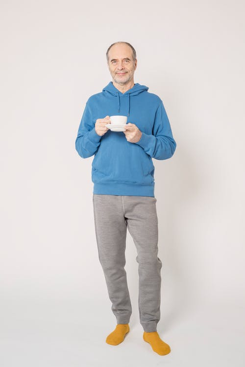 Man in Blue Hoodie Holding Cup