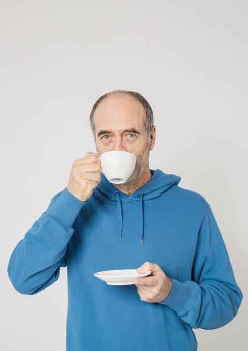 Man in Blue Hoodie Holding White Ceramic Mug