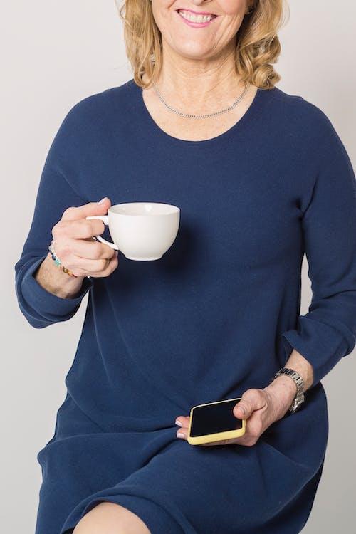 Woman in Blue Dress Holding White Ceramic Mug