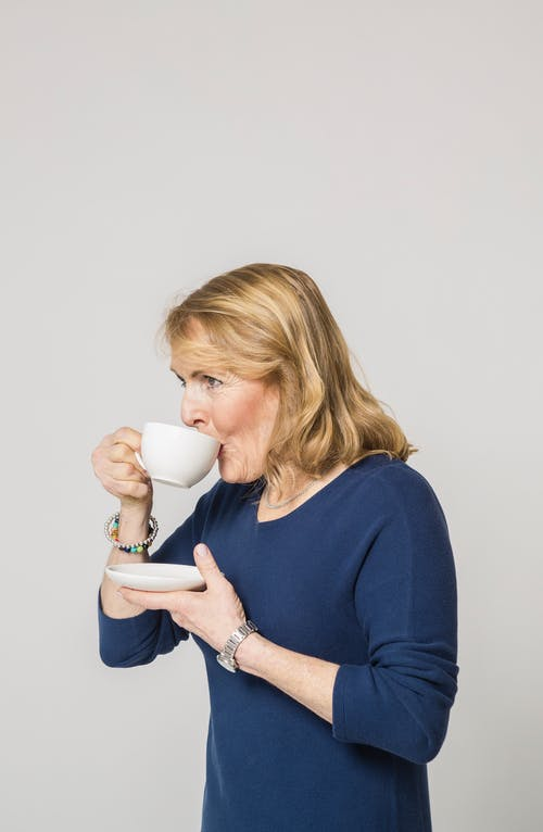 Woman in Blue Long Sleeve Dress Drinking from White Ceramic Mug