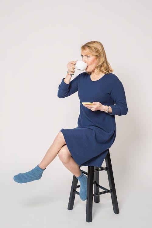 Woman in Blue Long Sleeve Dress Sitting on Bar Stool