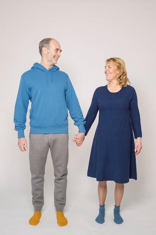 Man in Blue Long Sleeve Shirt Beside Woman in Blue Dress