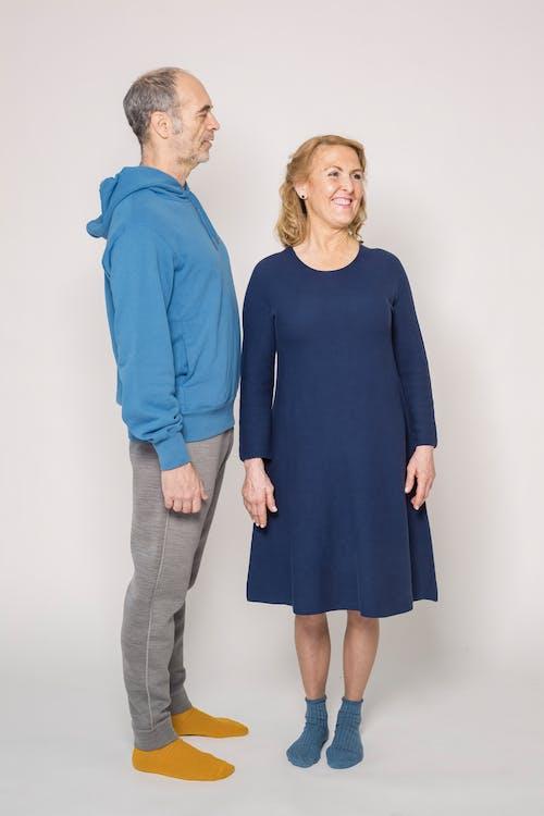 Woman in Blue Dress Beside Man in Blue Long Sleeve Shirt