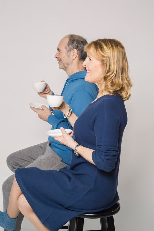 Man and Woman Sitting on Chair Holding Cup of Coffee