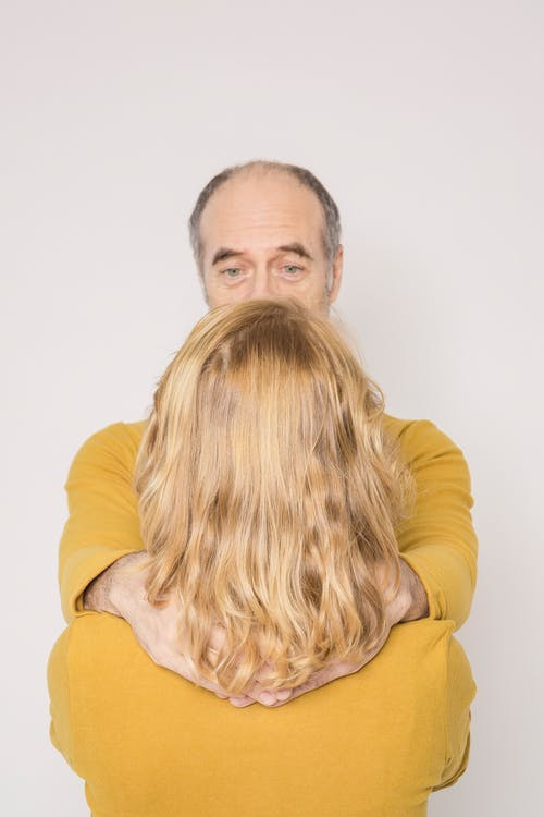 Back view of unrecognizable woman with elderly husband in similar outfits embracing and looking at each other against white background