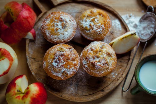 Top view of delicious baked muffins with powdered sugar placed near cut healthy apples in kitchen
