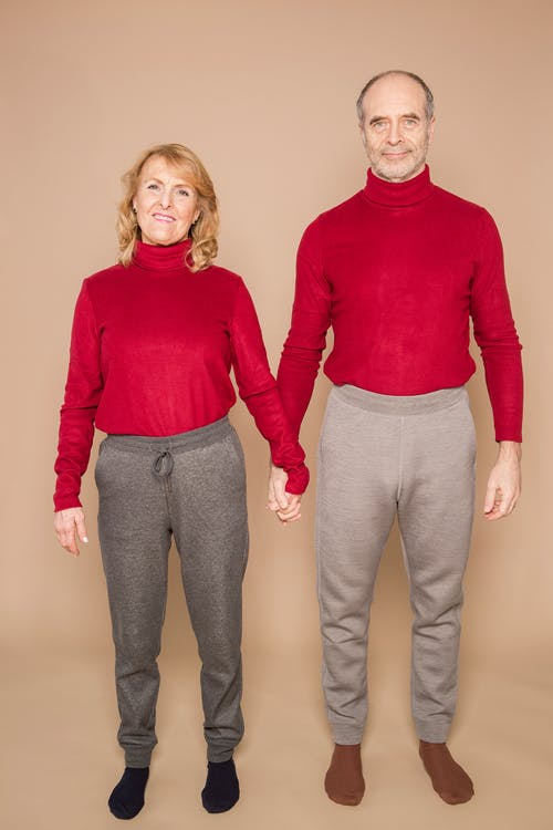 Man in Red Sweater Beside Woman in Red Long Sleeve Shirt