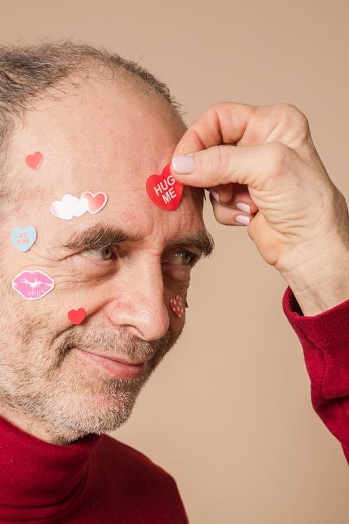 Man in Red Shirt With Heart Shaped Stickers on Face