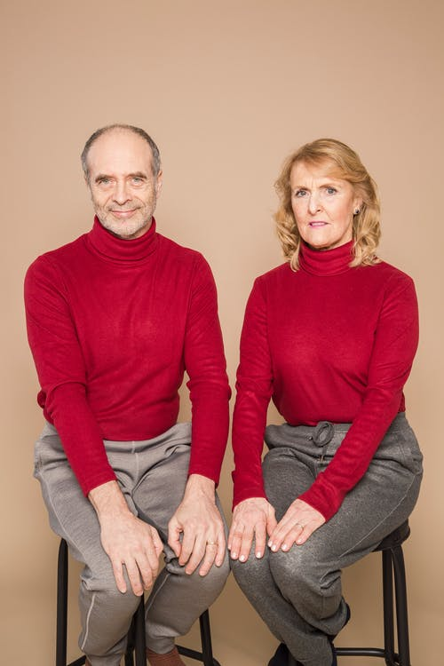 Man in Red Long Sleeve Shirt Sitting Beside Woman in Red Long Sleeve Shirt
