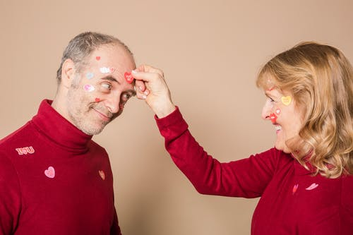 Woman Putting Stickers on Man's Face
